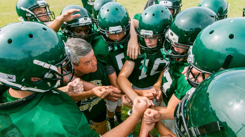 Football Team Huddle - Keswick Athletics Program